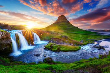 Gorgeous landscape with rising sun on Kirkjufellsfoss waterfall and Kirkjufell mountain, Iceland, Europe.
