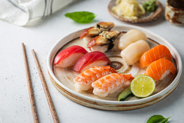 Set of sushi and maki on plate with soy sauce and chopsticks on white background. Top view with copy space