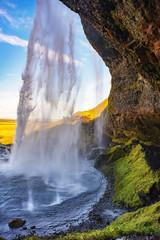 Seljalandfoss waterfall in sunny autumn day, Iceland. Famous tourist attraction