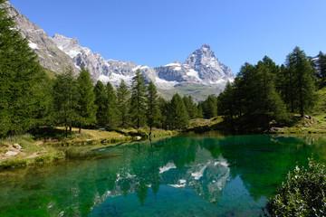 Panorama del paesaggio del lago azzurro con il riflesso nell'acqua della montagna del cervino e degli alberi circostanti in una radura alpina