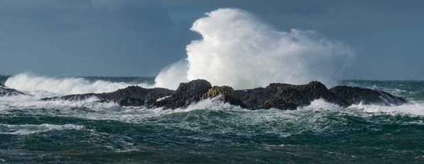 Massive waves crash over the rocks at Ballintoy Harbour, Causeway Coast, Northern Ireland