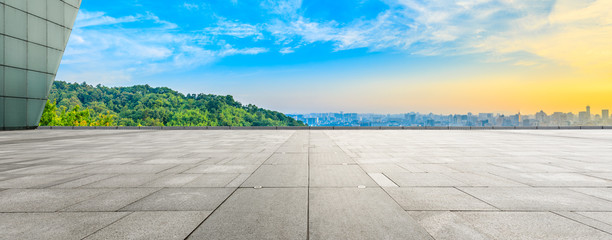 Wide square floor and city skyline with green mountain at sunrise in Hangzhou,China.