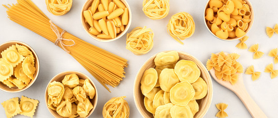 Flat lay with different types of traditional italian pasta. Penne, tagliatelle, fusilli, farfalle, spaghetti and others. Traditional italian cusine concept. Top view