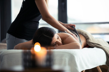Young woman removing the chocolate cream with towel to a pretty woman on the spa center.