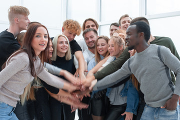 diverse young people putting their hands together