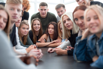 many diverse young people sitting at one table
