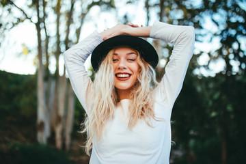 Chica felíz rubia con sombrero con fondo natural verde.