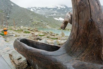 Water pipe with basin made out of old wooden trunk.