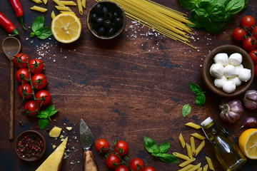 Traditional ingredients of italian cuisine : pasta, cheese,tomatoes,garlic,olive oil, basil and lemons. Top view with copy space.
