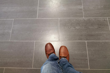 Legs in jeans and red shoes against the background of the tiled floor