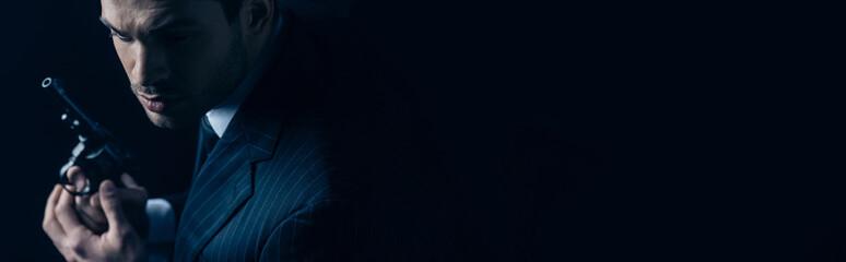 Gangster holding revolver on dark background, panoramic shot