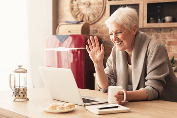 Elderly woman making video call on laptop in kitchen