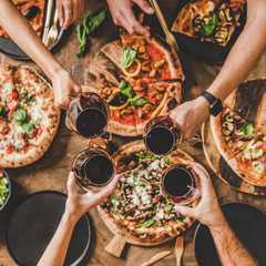 Family or friends having pizza party dinner. Flat-lay of people clinking glasses with red wine over rustic wooden table with various kinds of Italian pizza, top view, square crop. Fast food lunch
