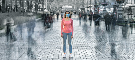 The young woman with medical mask on her face stands on the crowded street