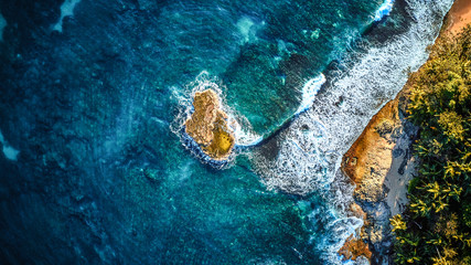 Aerial drone photo of a tiny island in a turquoise transparent water of an ocean, surrounded by sandy beach and palm trees of a tropical resort. View from the top