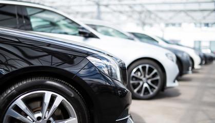 Neu- und Gebrauchtfahrzeuge stehen in einer Reihe vor einem Autohaus