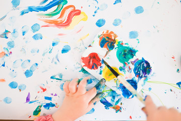 A child is painting with fingers and brush and oil paints