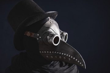 Masked man plague doctor, head profile, with bird mask and hat. Vintage style. Biohazard concept.