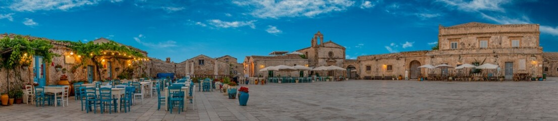 Panoramic view of the picturesque sicilian village Marzamemi, view of the traditional outdoor cafe and the church and the central square, province of Syracuse, Sicily, southern Italy