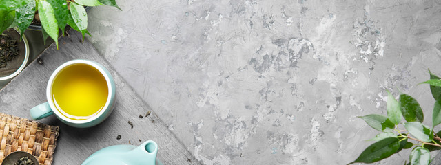 A cup of green tea in a blue cup on a gray concrete background. Cup of green tea with a teapot on a gray concrete background with copy space. Top view