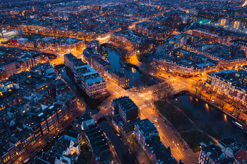 Amsterdam Netherlands aerial view at night. Old dancing houses, river Amstel, canals with bridges, old european city landscape from above.