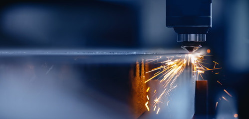 Blue color Laser CNC cut of metal with light spark, technology modern industrial