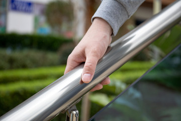male hand holds metal handrail in a public place
