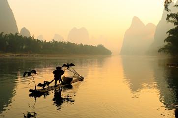 Silhouette of Fishing Men and His Cormorants on Li River at Sunrise, Guilin, China. The Li River or Lijiang is a river in Guangxi Zhuang Autonomous Region, China.