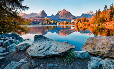 Last sunlight glowing of mountain hills on Strbske pleso lake. Exciting evening scene of High Tatras National Park, Slovakia, Europe. Beauty of nature concept background.