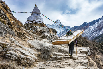 Sherpa carrying heavy woods for doors on the way to the Everest base camp, Himalaya mountains, Nepal.
