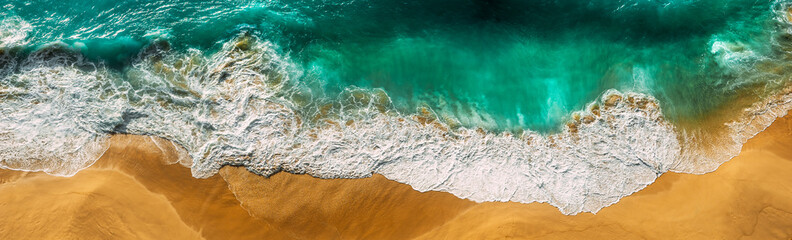 Beautiful sea wave at sunset from a bird's eye view. Beautiful lonely beach at sunset. Aerial view of turquoise ocean waves in Kelingking beach, Nusa penida Island in Bali, Indonesia. Beaches of Bali