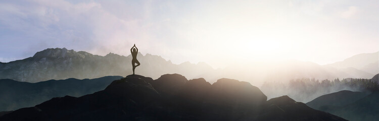 woman doing yoga on top of the mountain