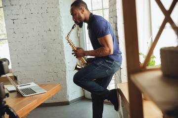 African-american musician playing saxophone during online concert at home isolated and quarantined. Using camera, laptop, streaming, recording courses. Concept of art, support, music, hobby, education