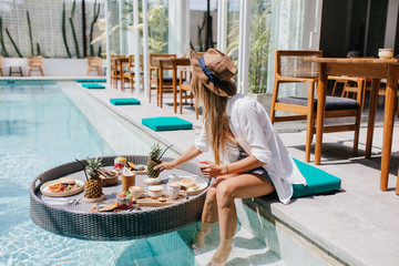Slim girl in elegant brown hat eating juicy fruits at resort cafe. Graceful european woman in white shirt relaxing with cocktail and food in pool.