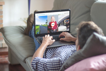 Man on the sofa using laptop with driving school online website on the screen