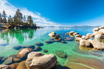 Lake Tahoe rocky shoreline in sunny day, beach with blue sky over clear transparent water