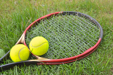 tennis racket and yellow balls lying on the grass, ready for training and games