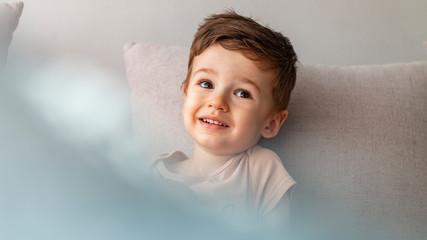 Portrait of happy joyful beautiful little boy. Close up portrait of an excited little boy laughing on gray background. Happy little boy at home. Bright closeup portrait of adorable happy toddler