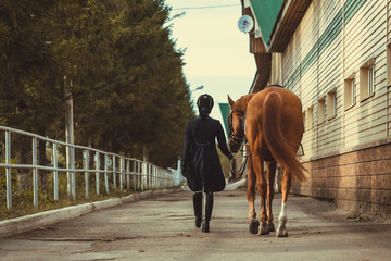 Rider woman with the horse are walking in a stable outdoors for dressage training