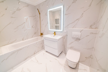 Bathroom with Italian tiles in light colors and modern lighting. Toilet and bath for human needs. Interior photos for designers and employees.