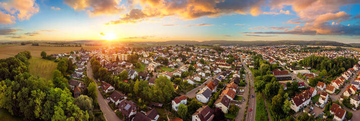 Aerial panorama of a small town at sunrise, with magnificent colorful sky and warm light