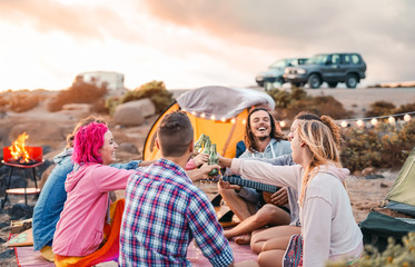 Happy friends toasting beers at barbecue camping party - Group young hipster people having fun dining and drinking together in campsite - Travel vacation lifestyle and youth culture concept