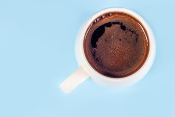 Black coffee in a white mug on a blue background