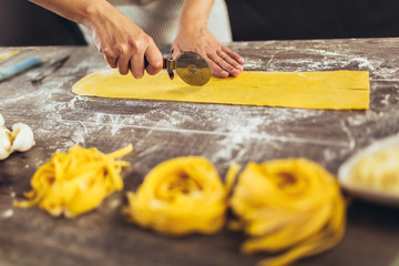 Woman cutting dough for ravioli on table
