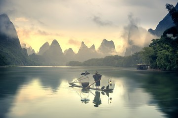 Guilin landscapes with a fisherman on a wooden boat on the water under the sunlight in Chian