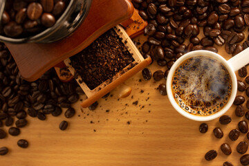 top view coffee cup with coffee grinder on wooden background.
