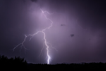 Dramatic lighting bolt falling during the night in Romania over rural area