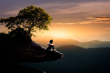 silhouette of a man sitting on a rock