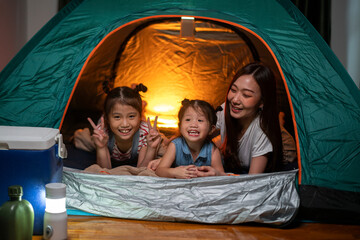 Asian woman playing and staying in tent with her daughter and having fun with camping tent in their bedroom a staycation lifestyle a new normal for social distancing in coronavirus outbreak situation
