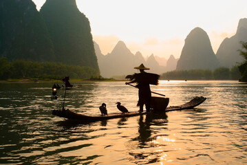 Silhouette of cormorant fisherman on the Li River (Lijiang) with karst peaks in the background at sunset, near Xingping, Guangxi Province, China